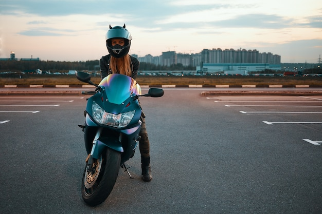 Full length isolated picture of fashionable active young female with blonde hair wearing safety helmet posing against multi storied buildings, sitting on motorbike with one foot on pavement Free Photo