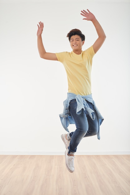 Full length of joyous asian guy dancing Free Photo
