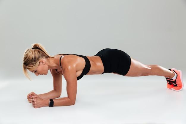 Полная длина сосредоточенной мускулистой спортсменки, делающей упражнения доски Бесплатные Фотографии