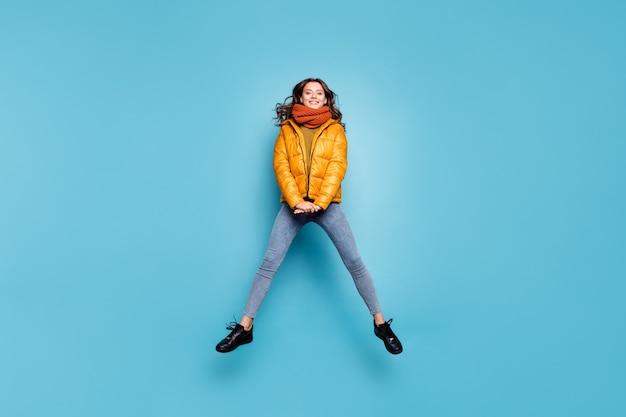 놀라운 귀여운 모델 레이디 점프 높은 착용 세련된 윈드 브레이커의 전체 길이 프리미엄 사진