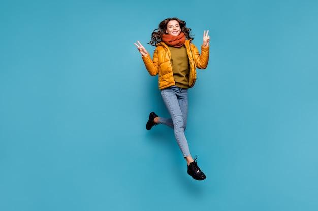 놀라운 모델 레이디의 전체 길이 점프 높은 흥분 보여주는 V 기호 프리미엄 사진