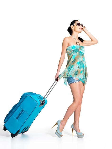 Полная длина повседневной женщины, стоящей с дорожным чемоданом Бесплатные Фотографии