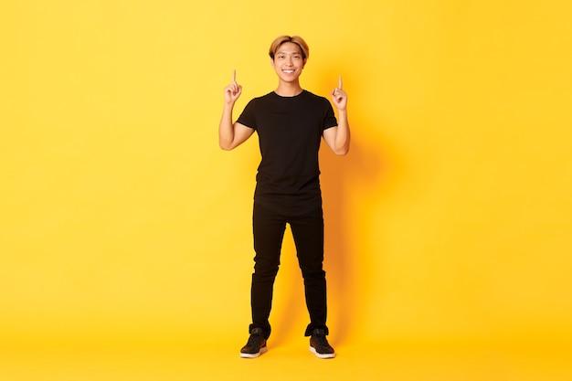 金髪の自信を持ってハンサムなアジア人男性のフルレングス。笑顔と指を上に向けて、ロゴと黄色の壁を見せています。 Premium写真