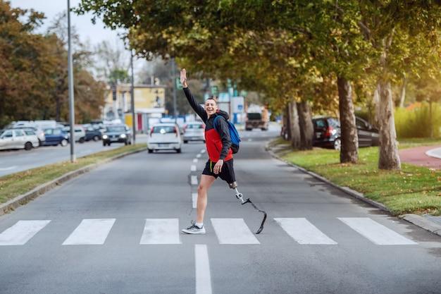 スポーツウェアのハンサムな白人の障害者スポーツマンの全長。義足とバックパックが通りを横切り、友達に手を振っています。 Premium写真