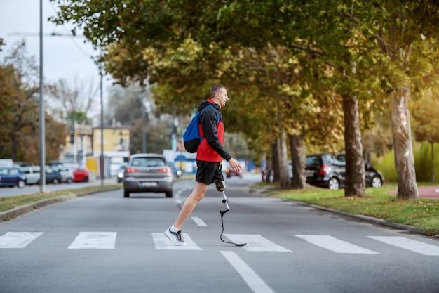 スポーツウェアのハンサムな白人障害者スポーツマンの全長、義足とバックパックの交差道路。 Premium写真