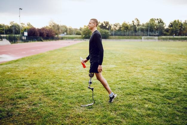 ハンサムなフィットの完全な長さの白人障害者のスポーティな男のスポーツウェアと義足サッカーコートの上を歩いて、軽食を保持しています。 Premium写真