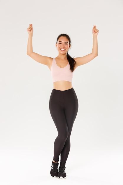 Полная длина тренировки стройной и здоровой азиатской улыбающейся девушки, стоящей в спортивной одежде и поднимающей руки вверх, как если бы держала табличку или баннер, рекламировала спортивный инвентарь или скидки на членство в тренажерном зале Premium Фотографии