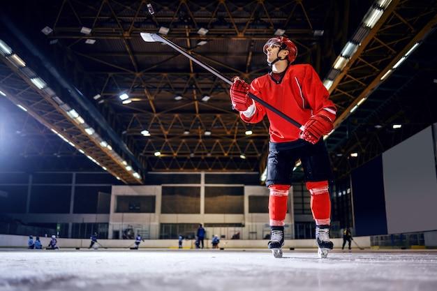 制服を着た強いホッケー選手の全長。ヘルメットを棒で振り、シュートをゴールに向けて準備する。 Premium写真