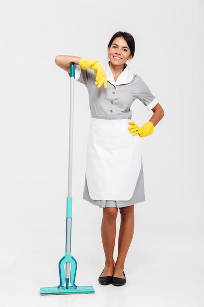 La foto integrale della domestica castana attraente in uniforme si è appoggiata la zazzera mentre stava Foto Gratuite