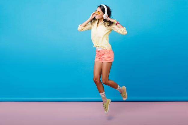 Foto integrale della ragazza caucasica sportiva spensierata che balla in scarpe da ginnastica. modello femminile asiatico brunetta felice in cuffie che salta, esprimendo emozioni felici. Foto Gratuite