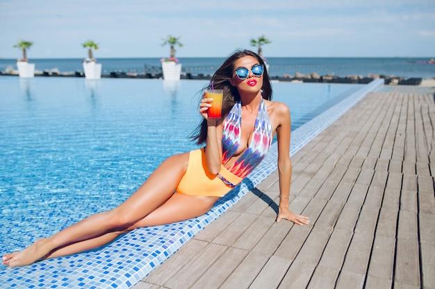 プールのそばに横になっている長い髪を持つ魅力的なブルネットの少女の全身写真。彼女はカラフルな水着とサングラスをかけ、足を水中に保ち、カクテルを持っています。 無料写真