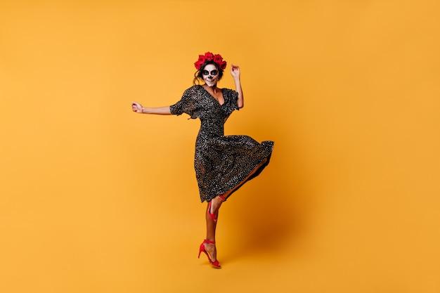 ハロウィーンのための化粧、かかとで焼夷弾のダンスと美しいドレスを着た魅力的な大胆な女性の全身写真 無料写真