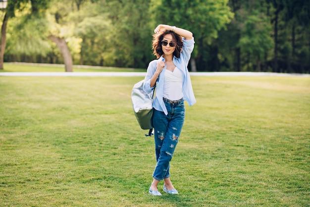 Фото в полный рост симпатичной девушки брюнет с короткими волосами в солнечных очках, позирующих в парке. она носит белую футболку, синюю рубашку и джинсы, туфли, сумку. она улыбается в камеру. Бесплатные Фотографии