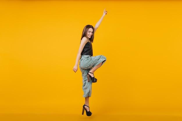 踊っているブルネットの女性の全身写真はハイヒールの靴を履いています。ジャンプする素敵な女の子の肖像画。 無料写真