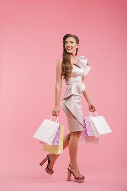 Copyspaceを振り返って、ピンクの壁に分離されたカラフルなショッピングパッケージを保持しているドレスを着た20代の女性の笑顔の全身写真 Premium写真