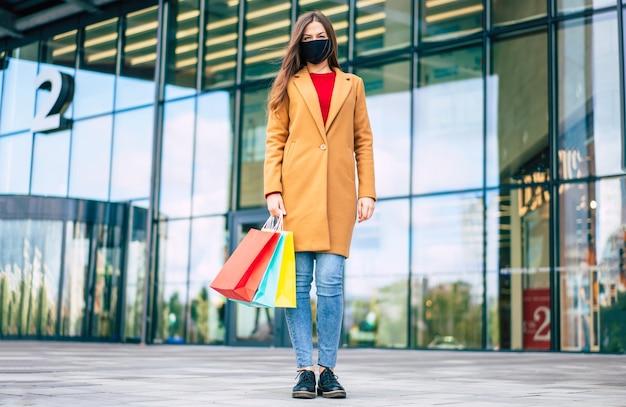 コートとショッピングバッグと安全医療マスクの若い自信を持っている女性の全身写真がモールの背景にポーズをとっています Premium写真