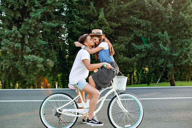Фото молодой пары в полный рост на велосипеде на дороге на фоне леса. парень в белой футболке едет на велосипеде и целует девушку, сидящую на руле Бесплатные Фотографии