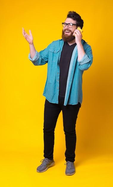 Полнометражное фото молодого человека, улыбающегося и говорящего на смартфоне на желтом фоне. Premium Фотографии