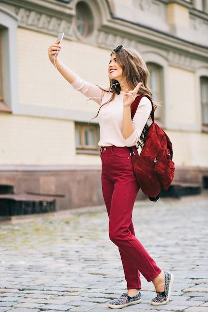 Foto a figura intera di bella ragazza con i capelli lunghi che fa selfie-ritratto sul telefono in città. ha un colore vinoso sui vestiti e sembra apprezzata. Foto Gratuite