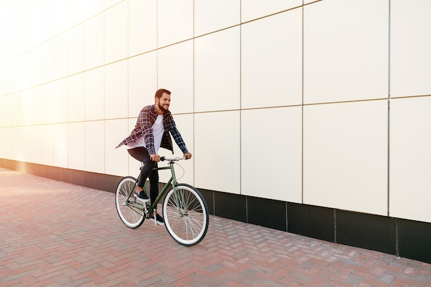 Full length photo of smiling young bearded man riding a bike on the city street. Free Photo