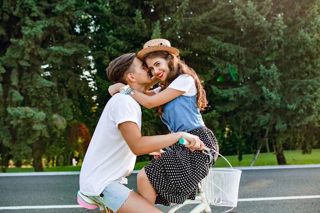 Foto a figura intera di giovane coppia innamorata in bicicletta su strada sullo sfondo della foresta. un ragazzo in maglietta bianca guida una bici e bacia una ragazza seduta sul manubrio Foto Gratuite