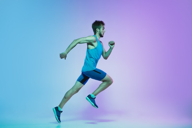 Full length portrait of active young caucasian running, jogging man on gradient studio in neon light Free Photo