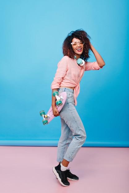 Ritratto integrale di attraente ragazza sportiva con pelle marrone che balla con il longboard. Foto Gratuite