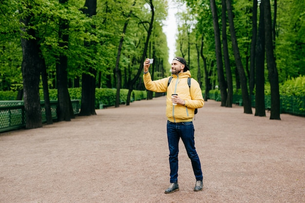Full length portrait of bearded young man dressed in yellow jacket, jeans and black cap having walk across green park Premium Photo