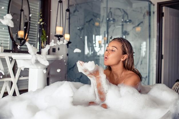 Full length portrait of beautiful brunette woman blowing foam while taking relaxing bath Premium Photo