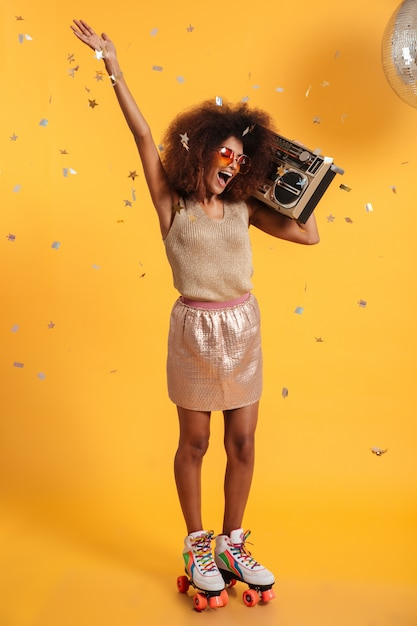 Full length portrait of beautiful overjoyed afro american disco woman with raised hand, standing on roller skates, holding boombox Free Photo