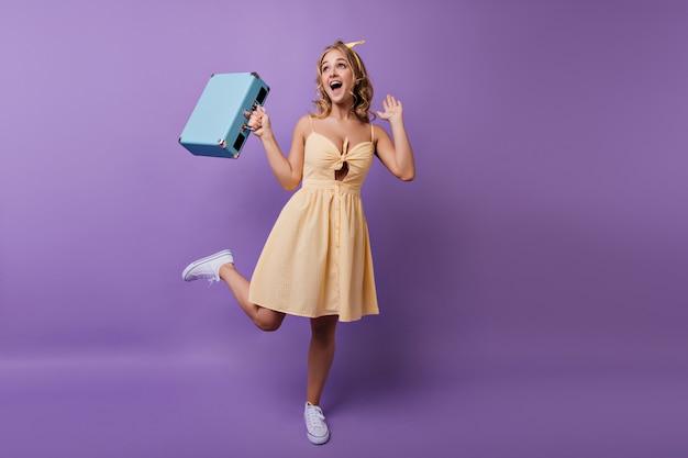 Ritratto integrale di beata ragazza sottile in abito giallo che balla prima del viaggio. ritratto dell'interno della giovane donna allegra riccia che esprime felicità. Foto Gratuite