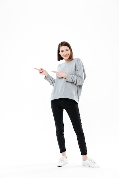Full length portrait of a casual woman pointing two fingers Free Photo