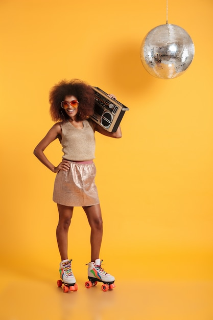 Full length portrait of cheerful african disco woman with hand on her waist wearing in retro clothes standing on roller skates, holding boombox Free Photo