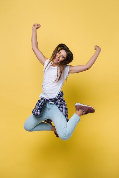 Full length portrait of a cheerful casual caucasian woman jumping Premium Photo