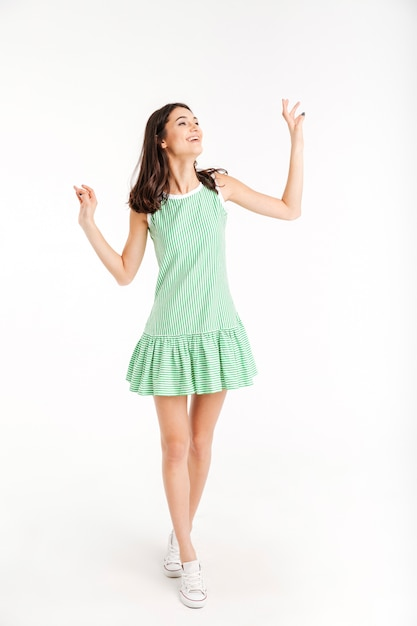 Full length portrait of a cheerful girl dressed in dress Free Photo