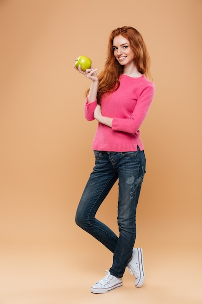 Full length portrait of a cheerful pretty redhead girl holding apple Free Photo