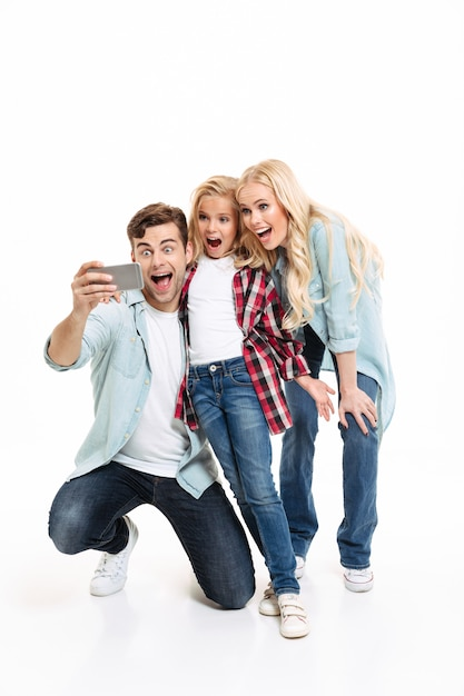 Full length portrait of a cheerful young family Free Photo