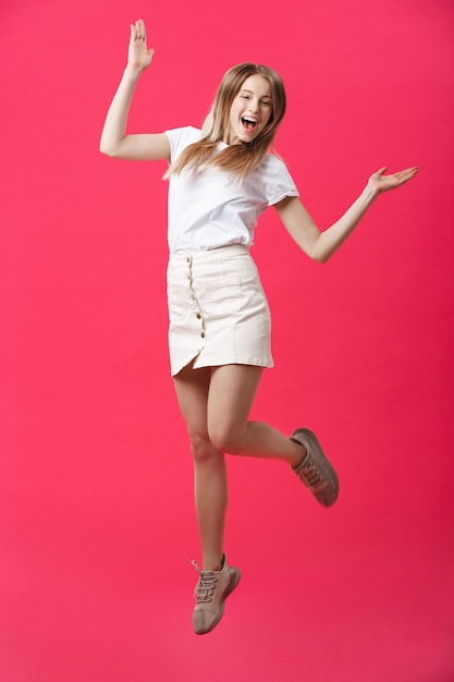 Full length portrait of a crazy joyful girl in casual cloth while jumping isolated over pink background Premium Photo