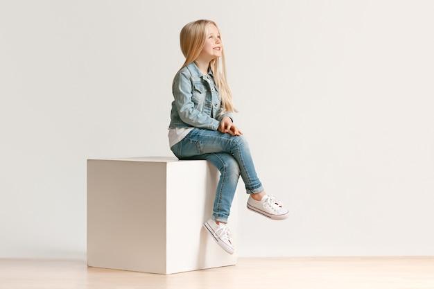 Ritratto integrale della bambina sveglia del bambino in vestiti alla moda dei jeans e sorridente, stante sul bianco. concetto di moda per bambini Foto Gratuite