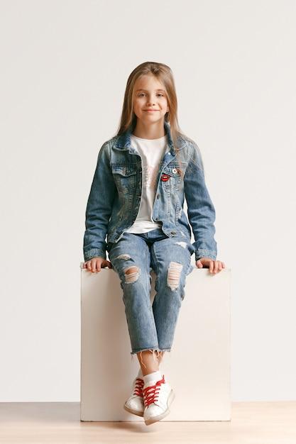 Ritratto integrale della piccola ragazza teenager sveglia in vestiti alla moda dei jeans che guarda l'obbiettivo e che sorride contro il muro bianco dello studio. concetto di moda per bambini Foto Gratuite