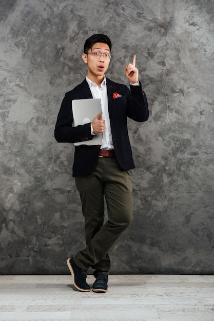 Full length portrait of an excited young asian man Premium Photo