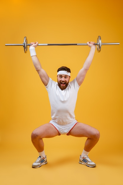 Full length portrait of a fitness man squatting with barbell Free Photo