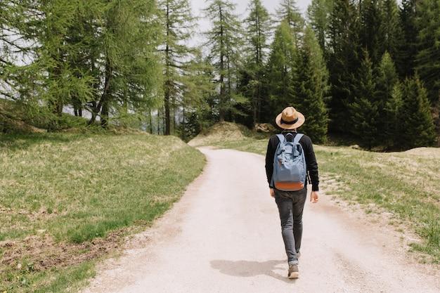 휴가에 여름 숲을 탐험하는 남성 여행자의 뒤에서 전신 초상화 무료 사진