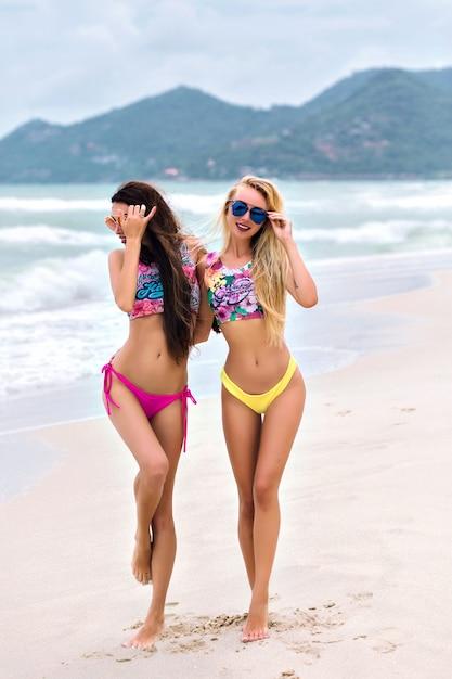 海岸を歩いて手を繋いでいる明るいビキニのスリムな女性の後ろからの全身像。長い髪で遊んで、エキゾチックな国で夏を楽しんでいる日焼けした女の子。 無料写真