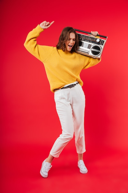 Full length portrait of a happy girl with a boombox Free Photo