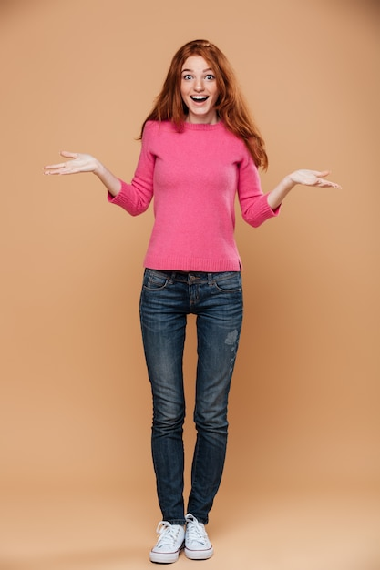 Full length portrait of a happy young redhead girl with open hands Free Photo