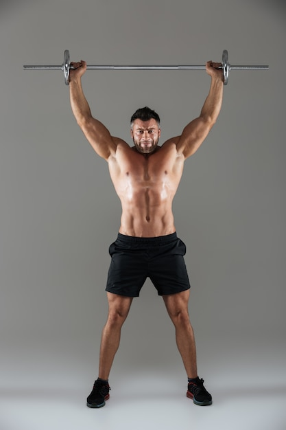 Full length portrait of a muscular serious shirtless male bodybuilder Free Photo