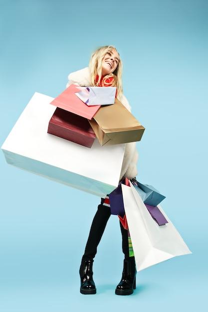 블루 스튜디오 배경 위에 절연 다채로운 쇼핑 가방과 함께 산책 아름 다운 미소 재미 금발 여자의 전체 길이 초상화. 무료 사진