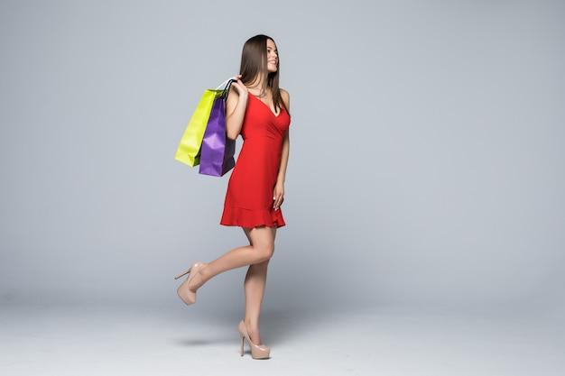 白い壁で隔離の買い物袋を保持している陽気な魅力的な女性の全身像 無料写真