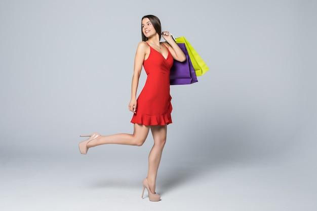 흰 벽에 고립 된 쇼핑 가방을 들고 쾌활한 매력적인 여자의 전체 길이 초상화 무료 사진